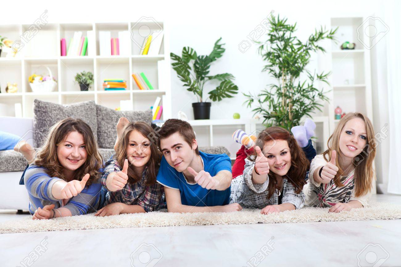 Group of happy young boy and girls lying down and holding thumbs up in the air Stock Photo - 13888138