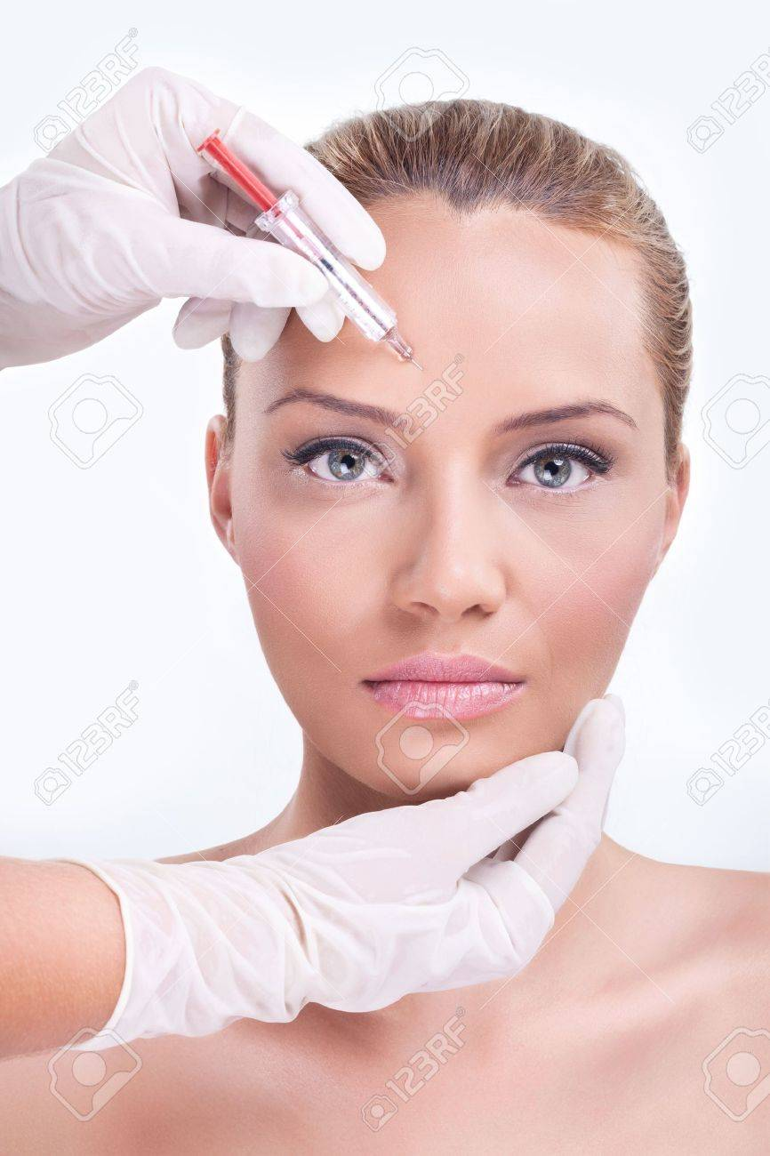 Woman receiving botox injection in the eyebrow zone stock photo woman  receiving botox injection in the