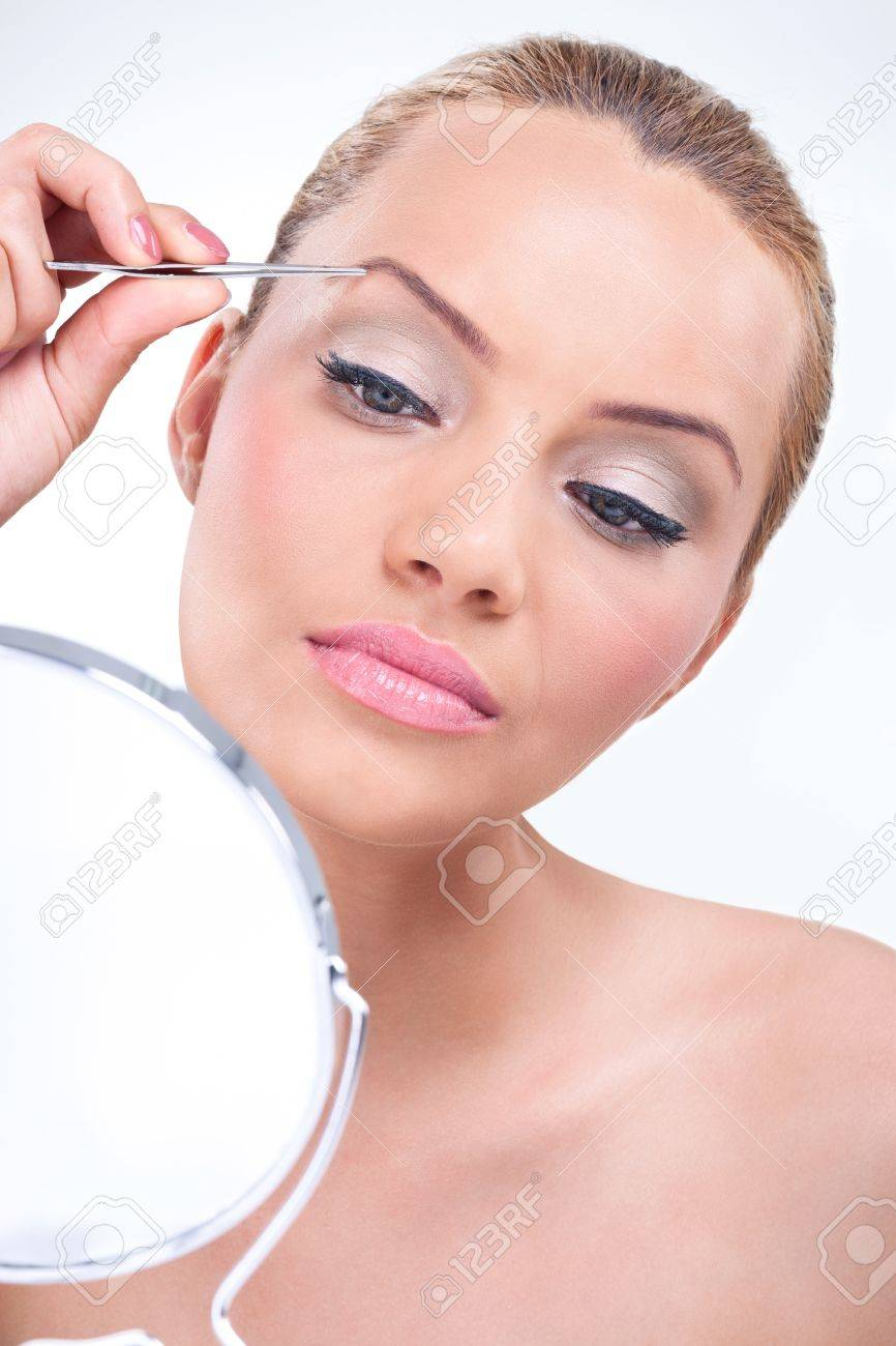 Attractive Woman Plucking Her Eyebrows And Looking In Mirror Stock