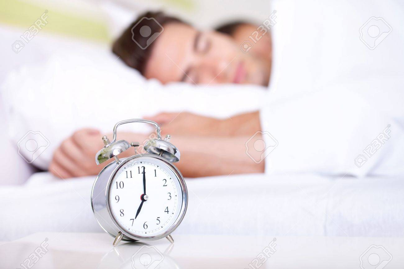 Young couple lying in white bed with silver alarm clock Stock Photo - 15038496