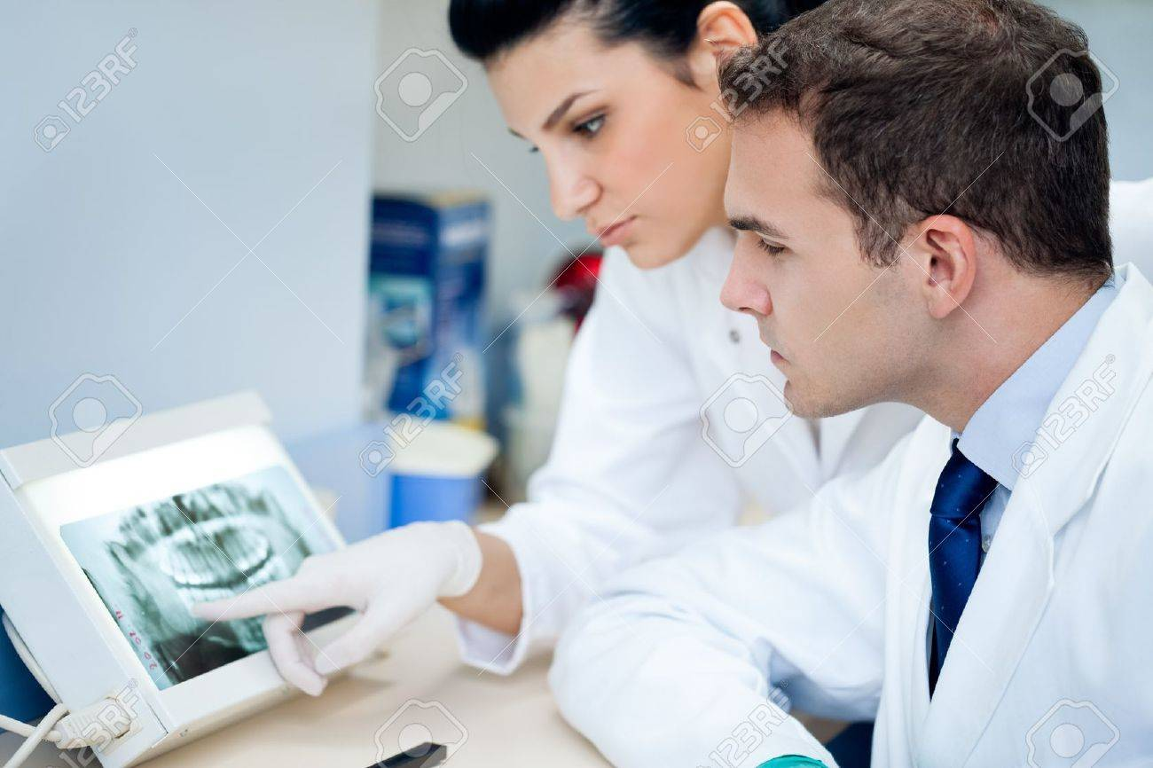 Dentis And Assistant Analyzing X-ray At The Dental Clinic Stock ...