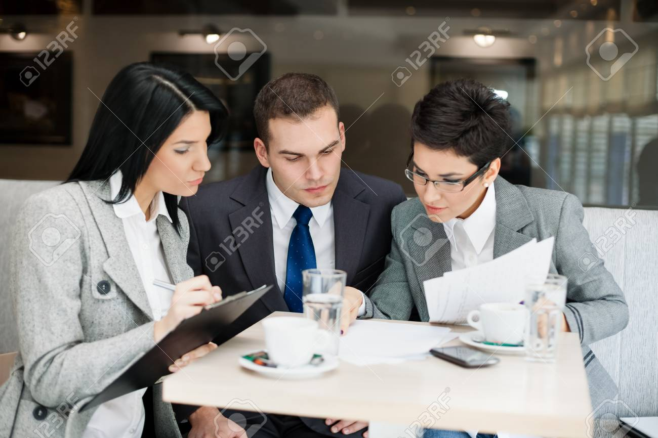 Young businesspeople having a business meeting at coffee table Stock Photo - 17821764