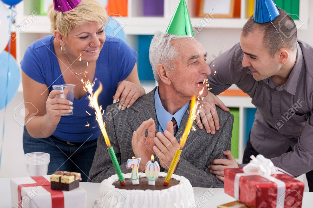 Party For 70th Birthday Senior Man Celebrating With His Family Stock Photo