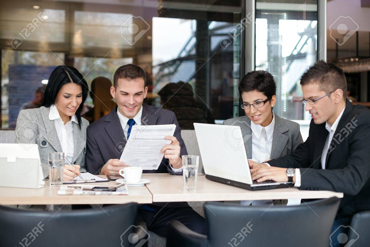 Group of young business people sitting at a table  and discussing an interesting idea in the cafe Stock Photo - 19404907