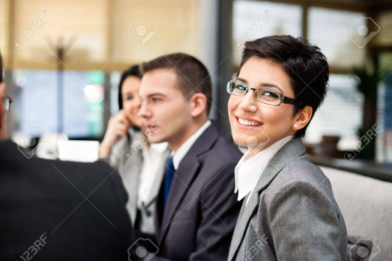 Closeup portrait of a smart young businesswoman smiling and her colleagues working Stock Photo - 19404696
