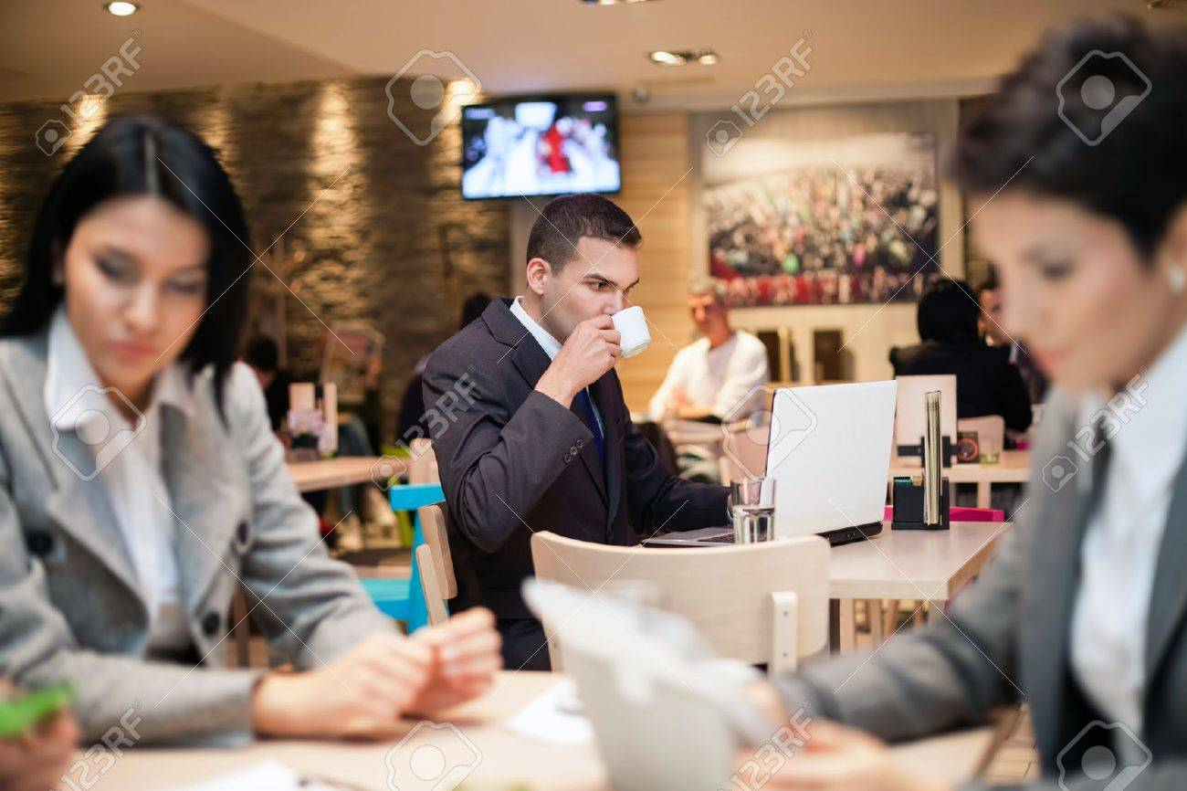 Businessman sitting alone in a cafe  with a coffee and reading the newspaper Stock Photo - 21260054