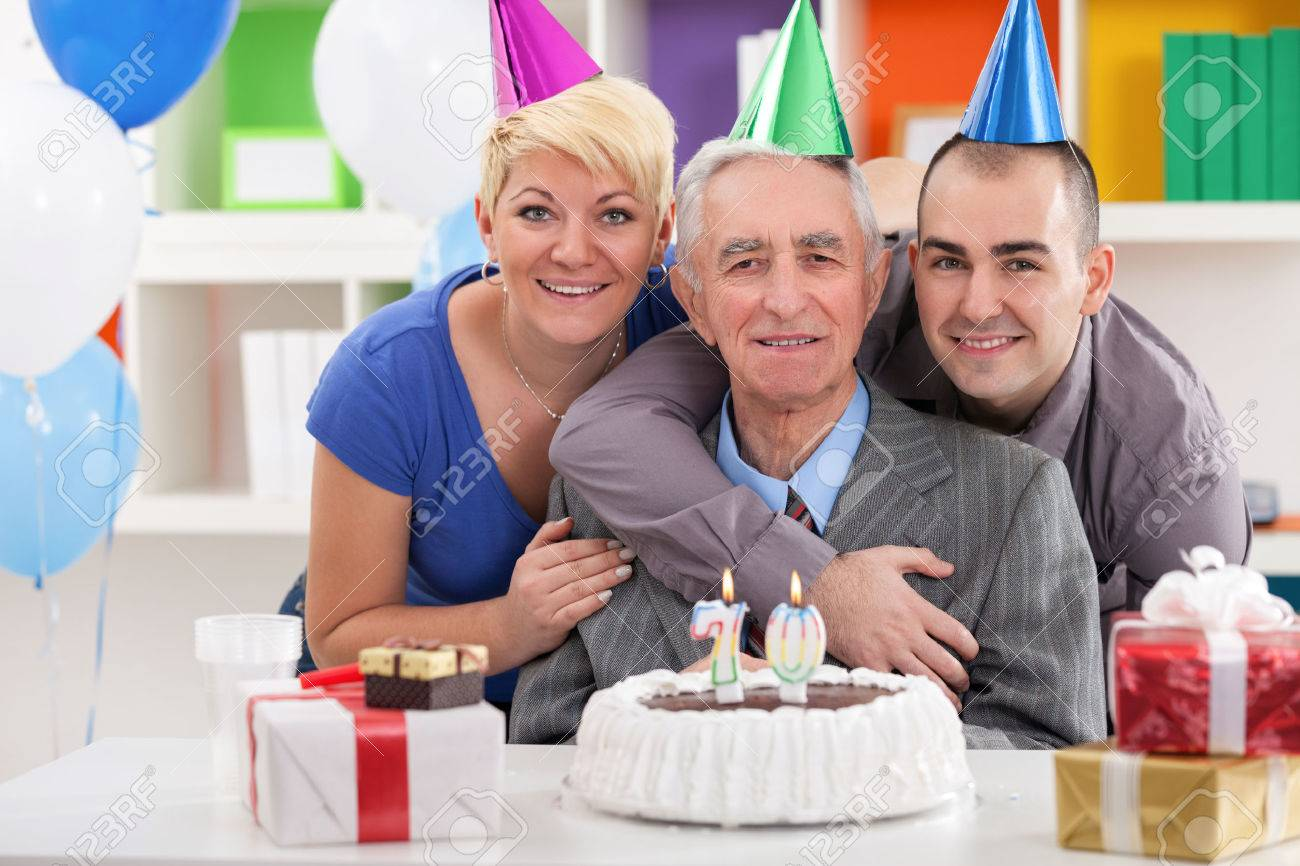 Portrait Of Happy Family Front Of Birthday Cake For 70th Birthday