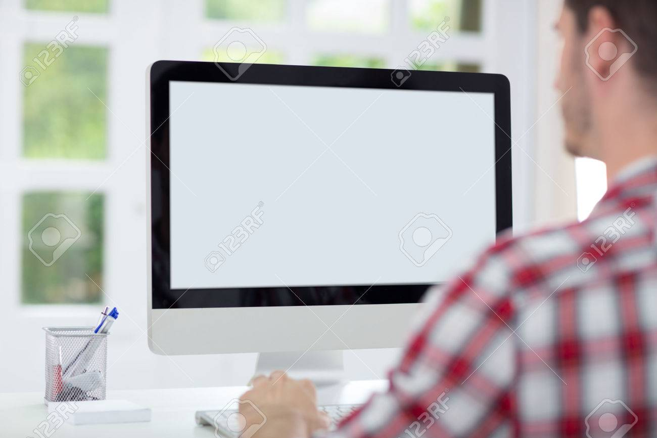 stock photo young man working in bright office looking at computer screen bright office