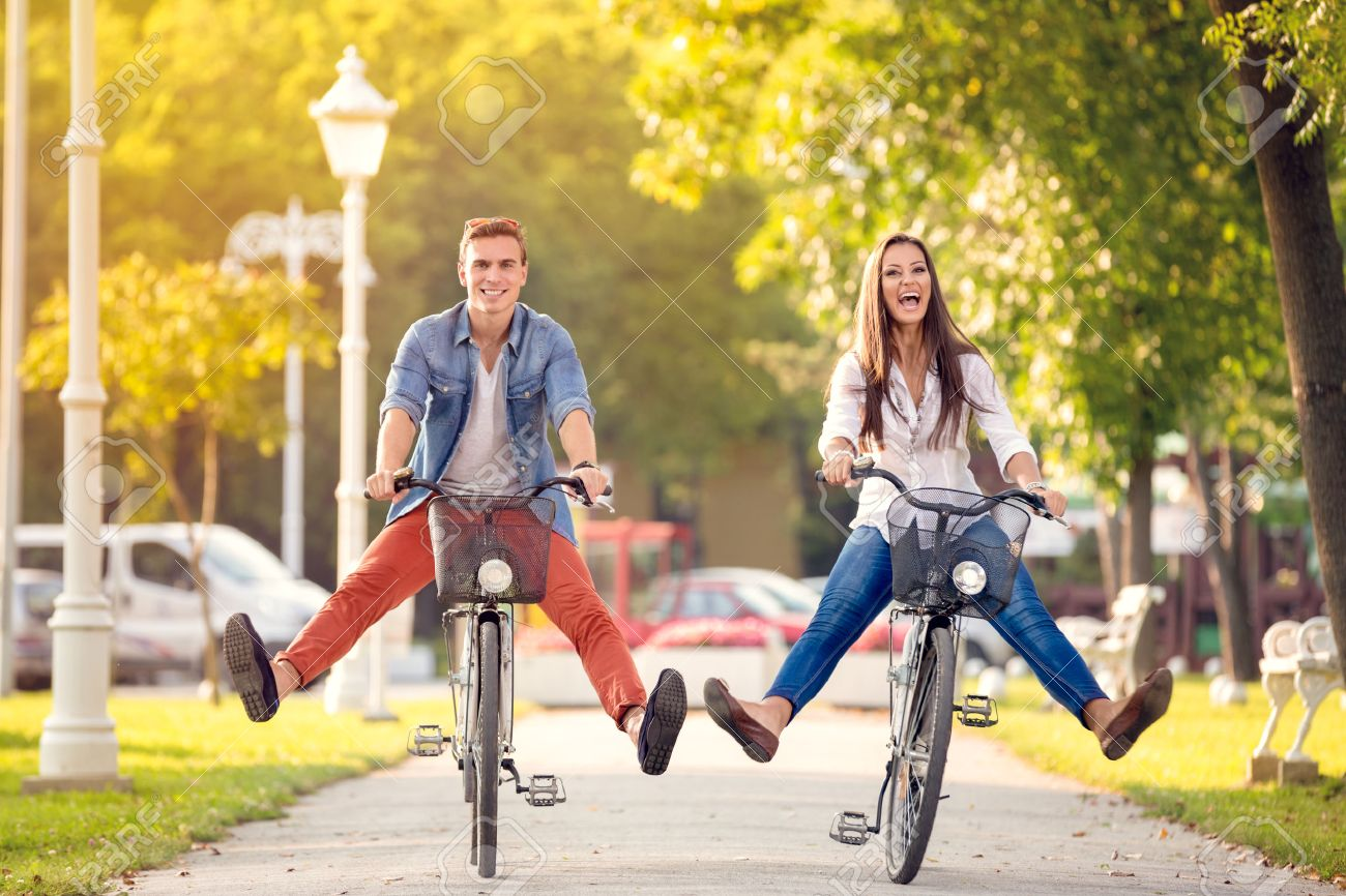 Happy funny young couple riding on bicycle Stock Photo - 42200269