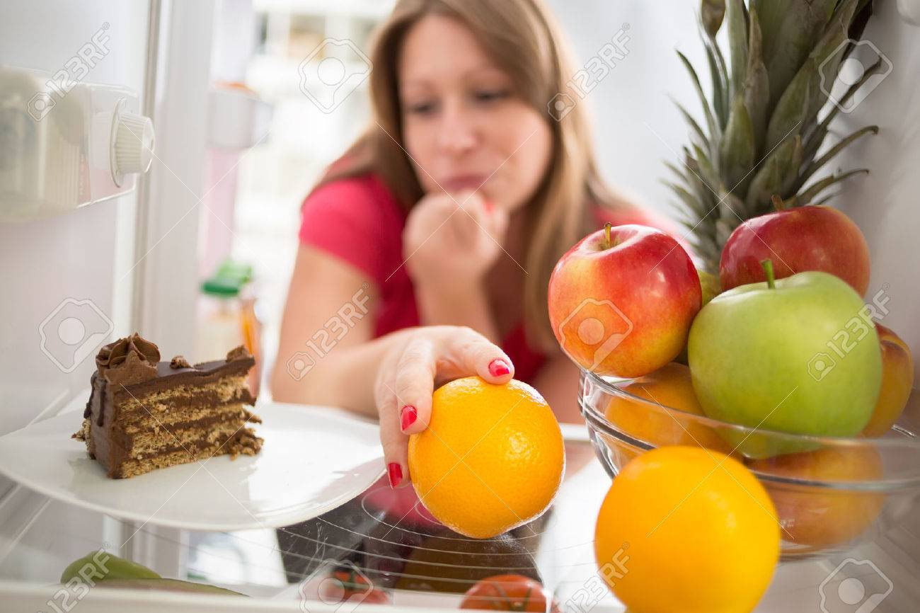 Woman hesitating whether to eat piece of chocolate cake or orange - 46627000