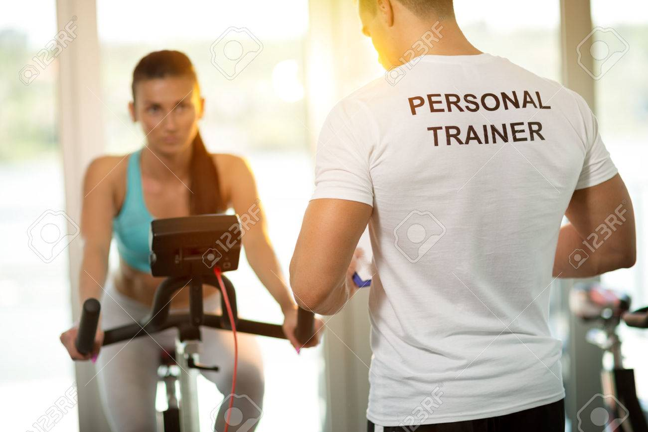 839ea258992 Personal trainer at the gym with client on bike Stock Photo - 48434633