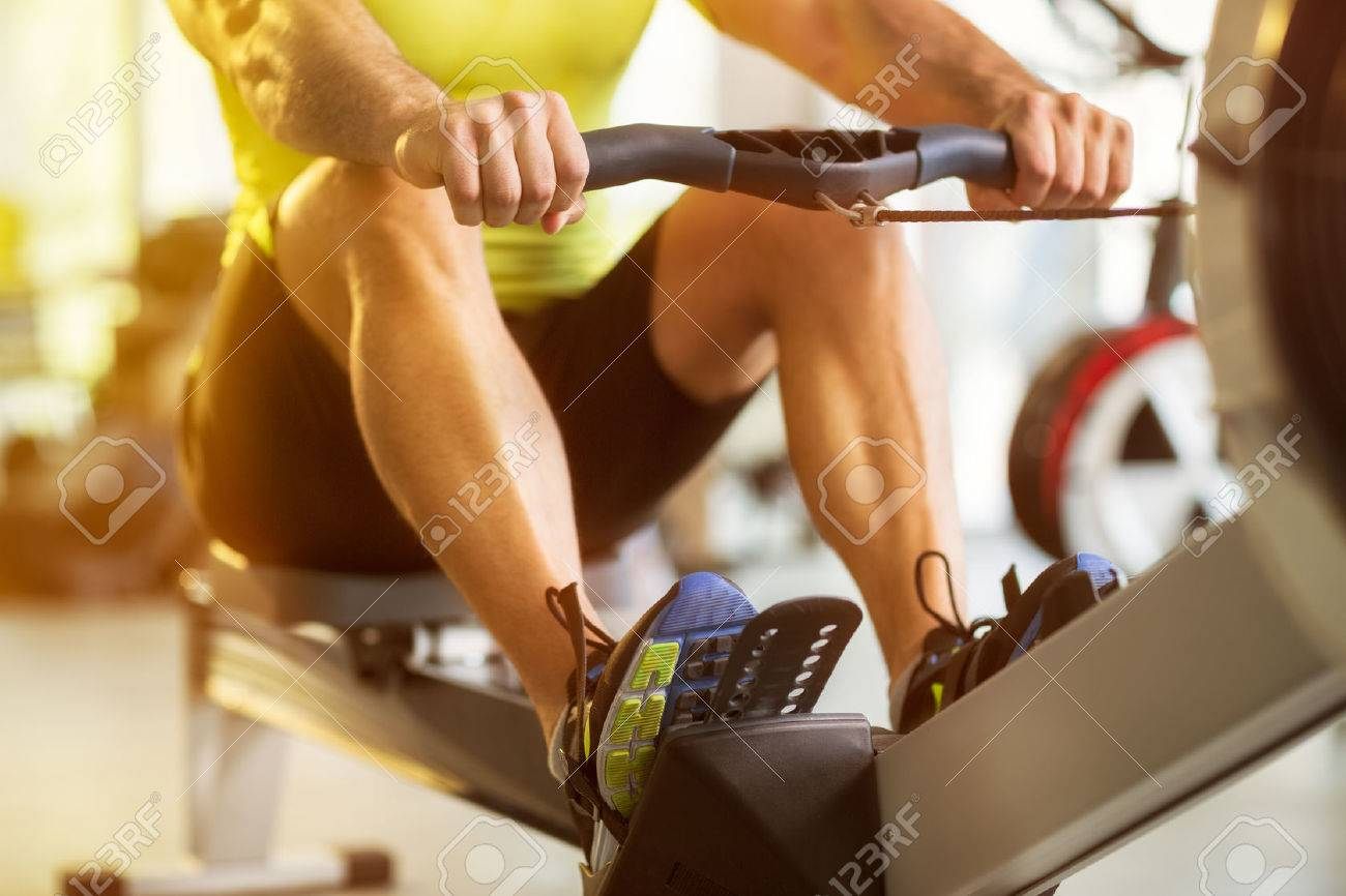 Fit man training on row machine in gym Stock Photo - 48434712