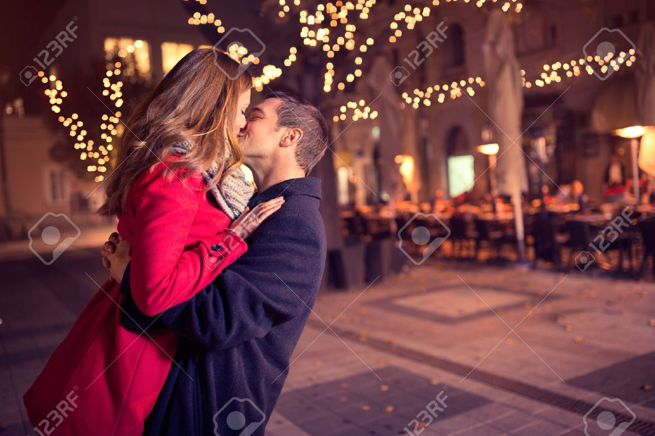 Young affectionate couple kissing tenderly on Christmas street Stock Photo - 48403802