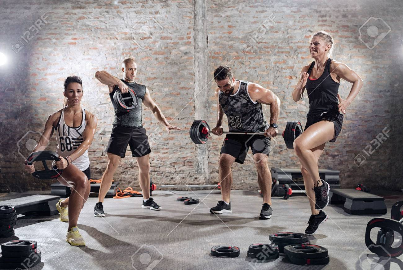 group of muscular sporty people practicing with weights Banque d'images - 55301139