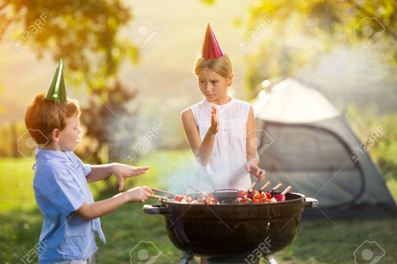 children having a barbecue party on camping - 55667732