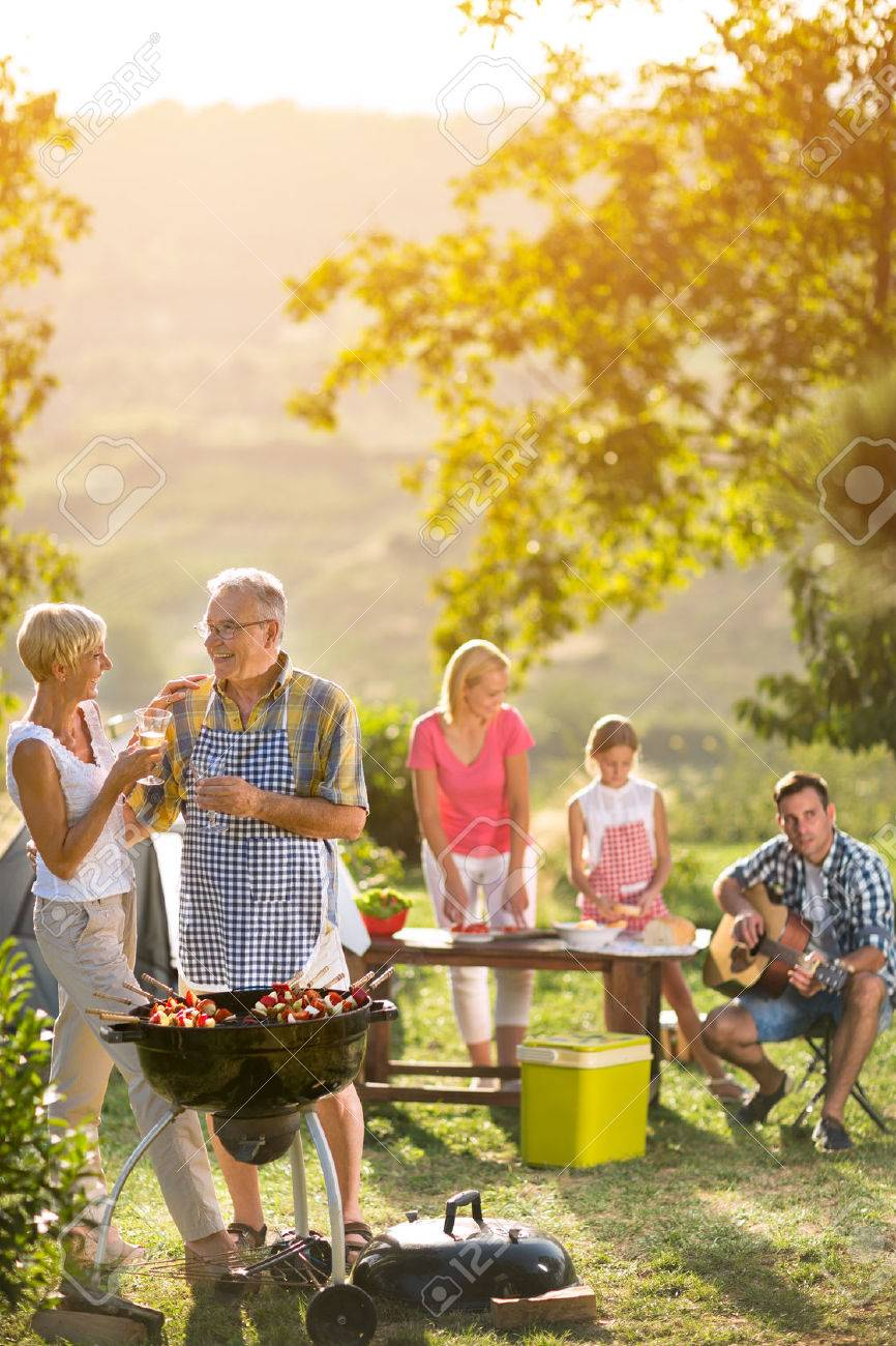 smiling grandparents drinking wine and enjoying picnic with family Banque d'images - 55714991