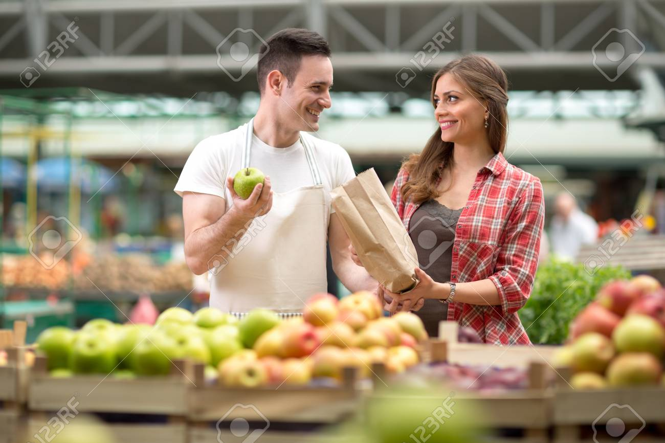 smile salesman presentation produces at the market stock photo