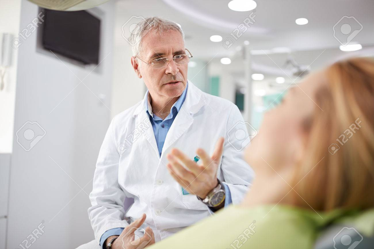 Male dentist on working place with female patient in dental practice - 61055672