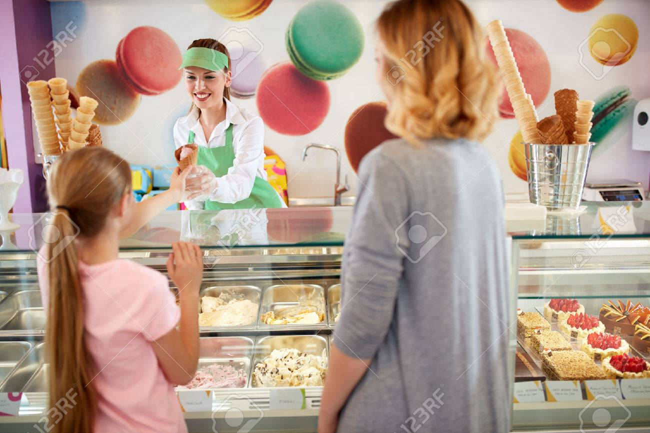 Female seller in bakery gives ice cream to girl Banque d'images - 61055727