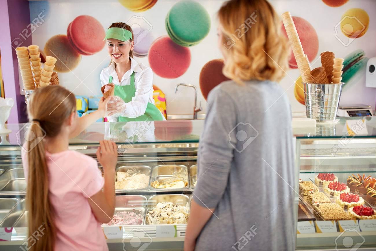 Female seller in bakery gives ice cream to girl - 61055727