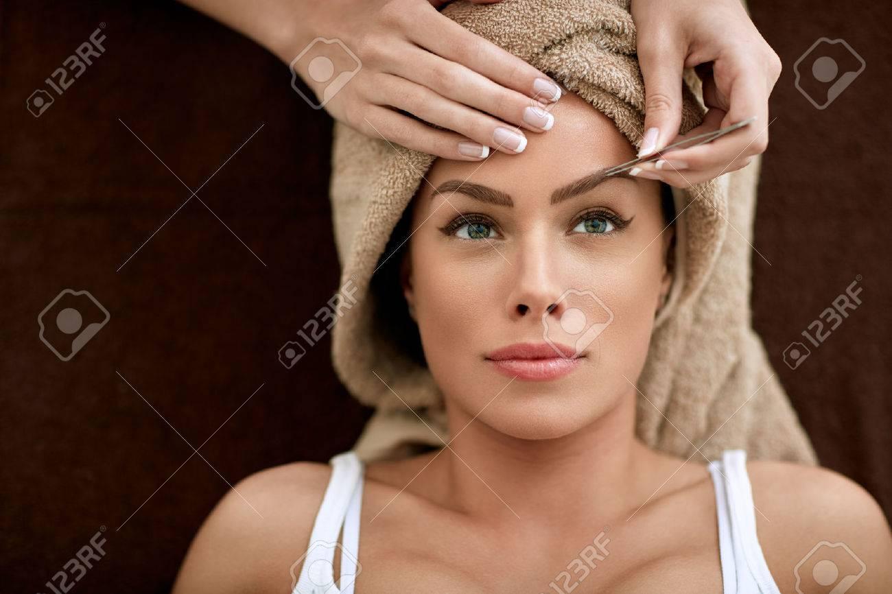 Beautiful woman receiving professional eyebrow shaping - 62524159