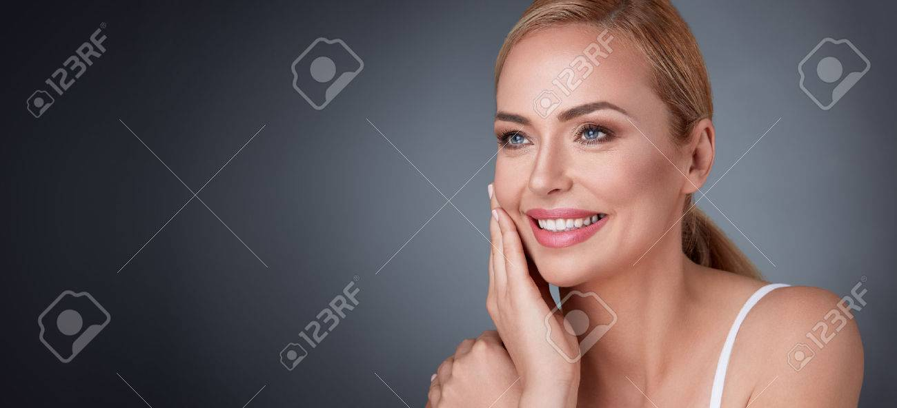 Smiling middle aged woman satisfied with her nature beauty Banque d'images - 64540809