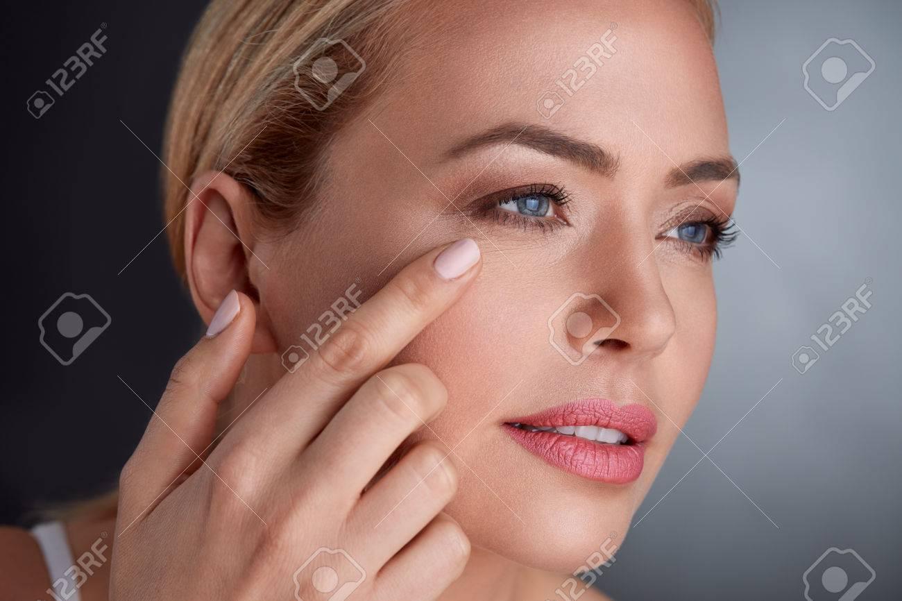 femme moyenne d'âge en regardant la peau sur son visage Banque d'images - 64540891