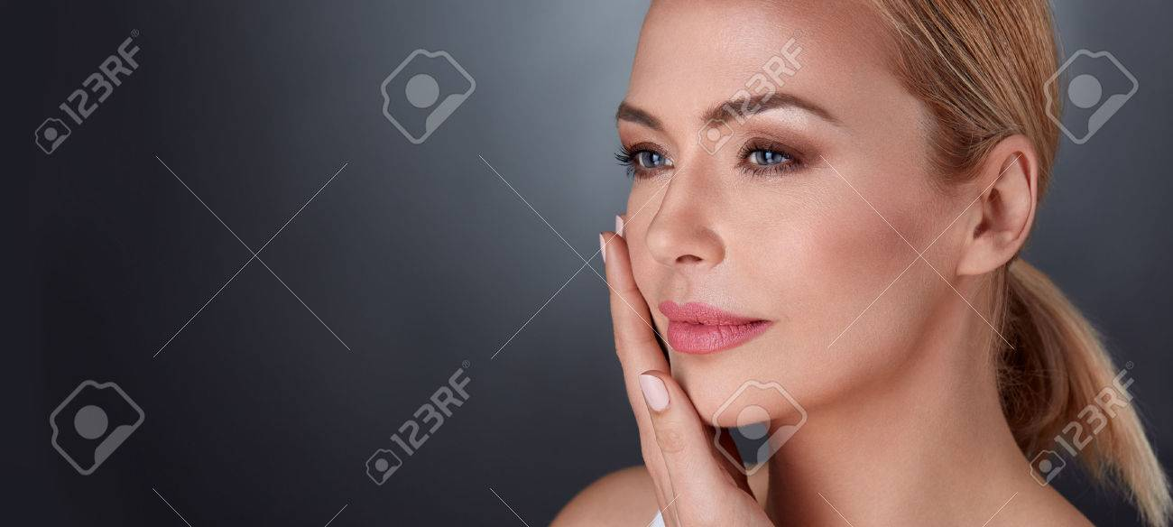 beautiful middle aged female touching her face skin and feel the softness - 65326671