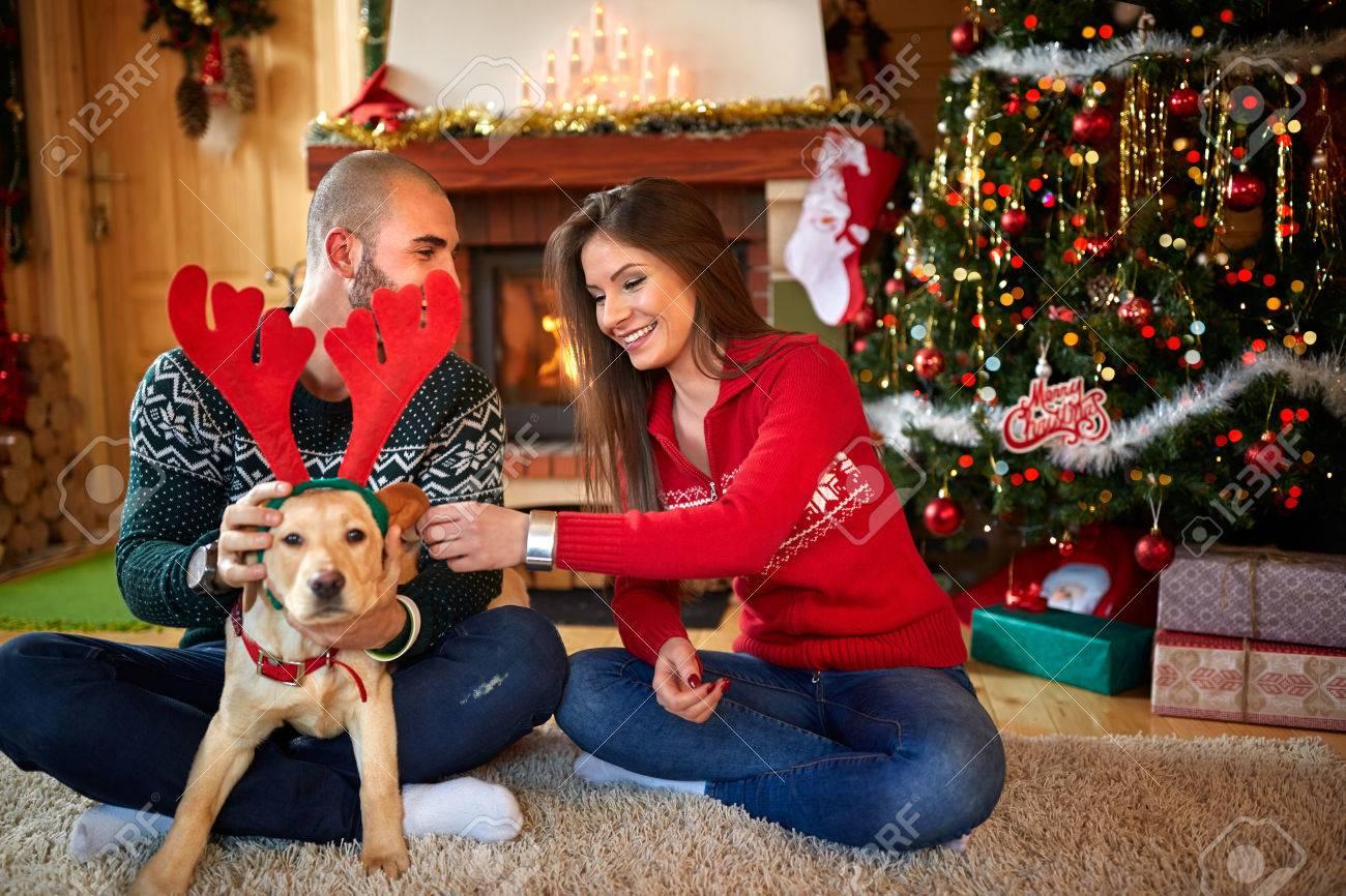 Junges Paar macht Spaß mit schönen Hund für Weihnachten
