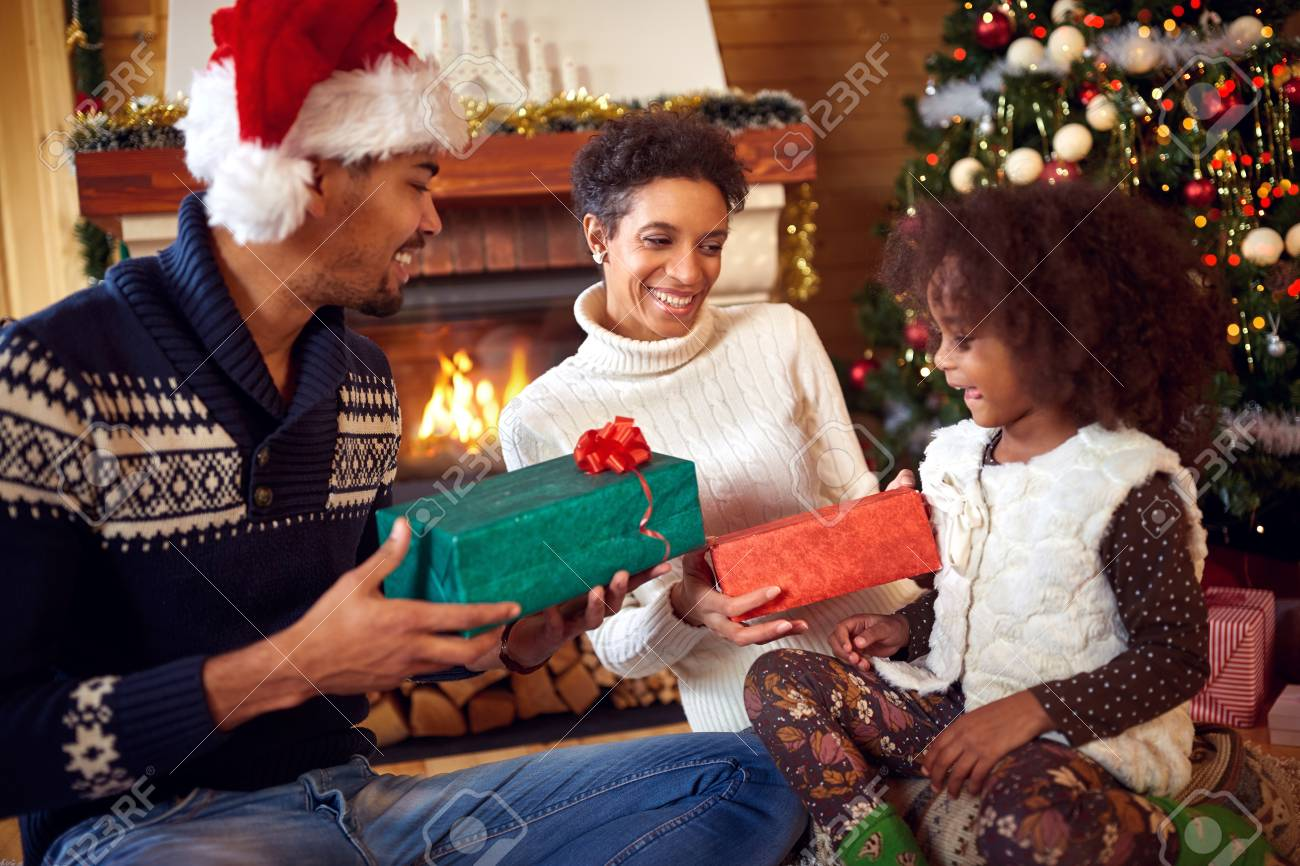 Christmas In Africa Traditions.Smiling African American Parent Give Christmas Present Their