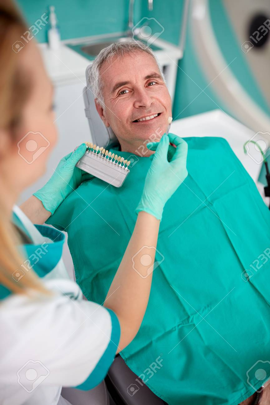 Senior man in dental clinic choosing color for teeth dentures