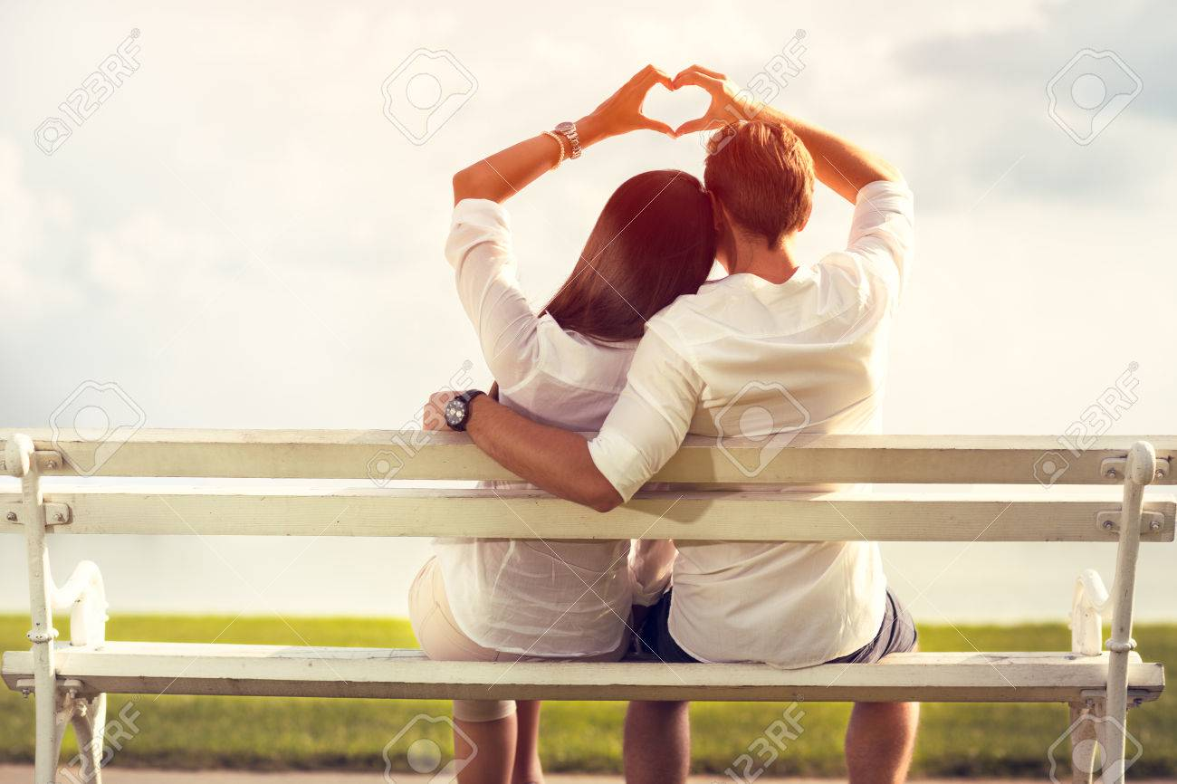 Affectionate Couple Making A Love Symbol With Hands Stock Photo