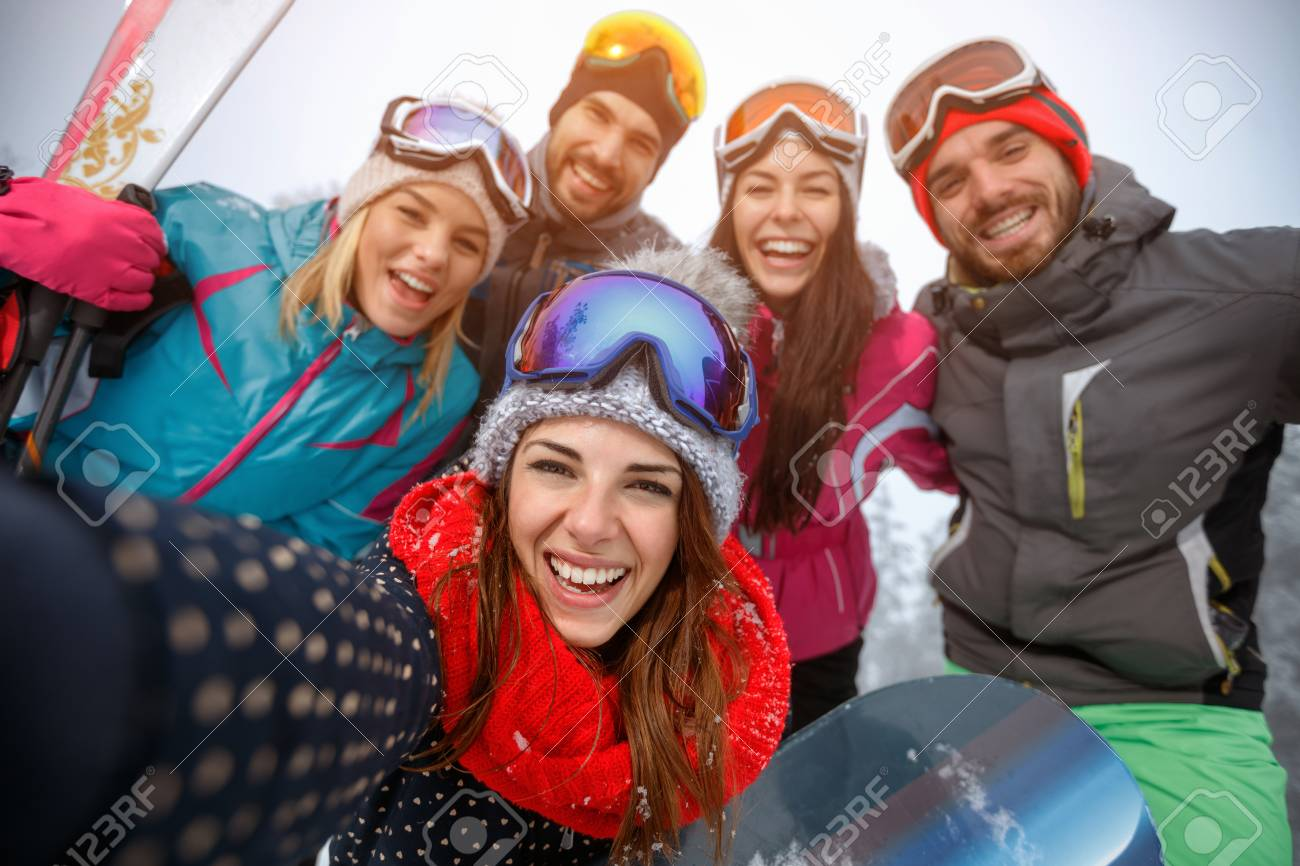 Group of smiling friends having fun on the snow and making selfie - 90235967