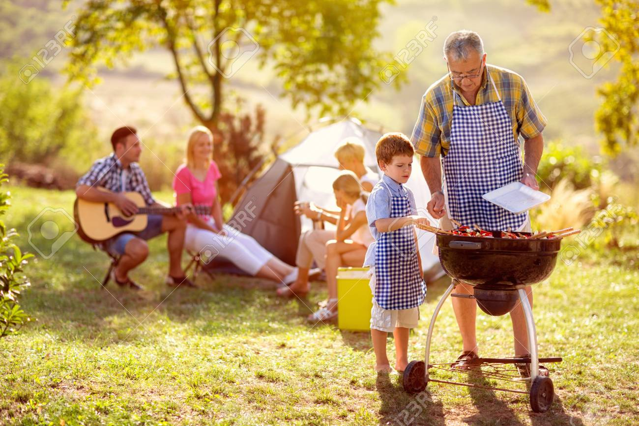 grandson cooking on campfire with grandfather on camping - 121569337