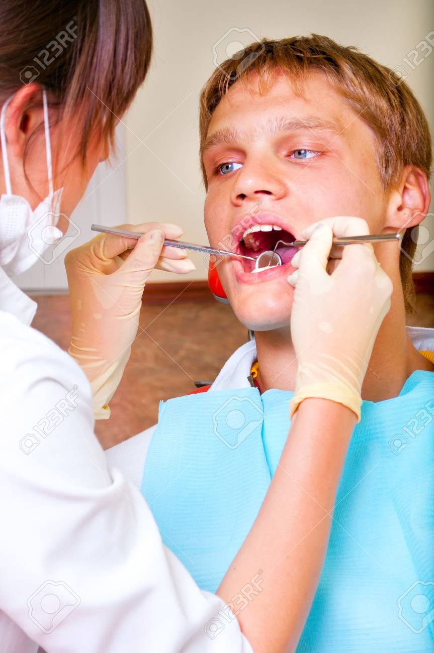 Young dentist giving a treatment to her patient Stock Photo - 7761981