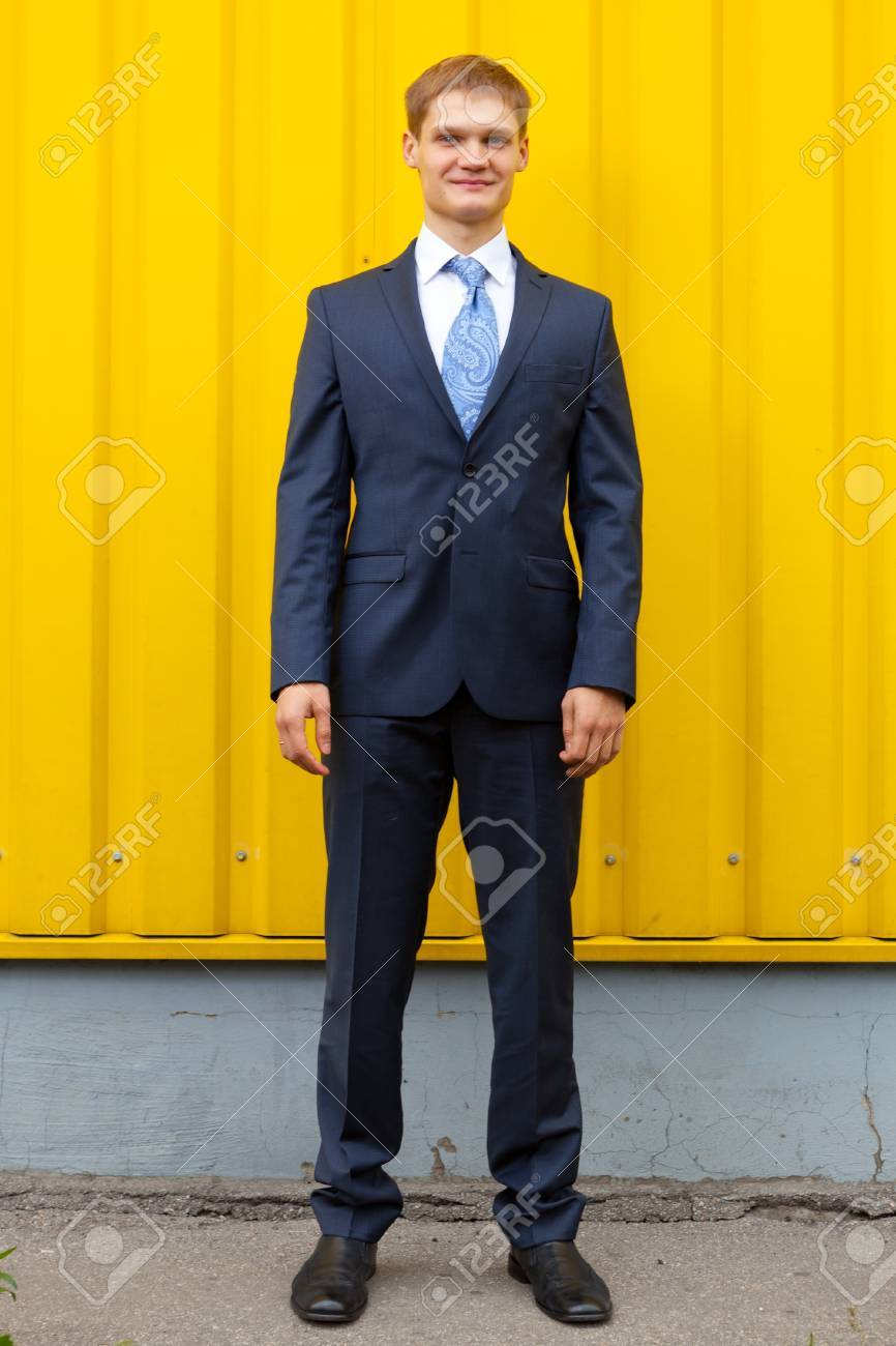 Optimistic Young man standing against yellow wall Stock Photo - 11792824