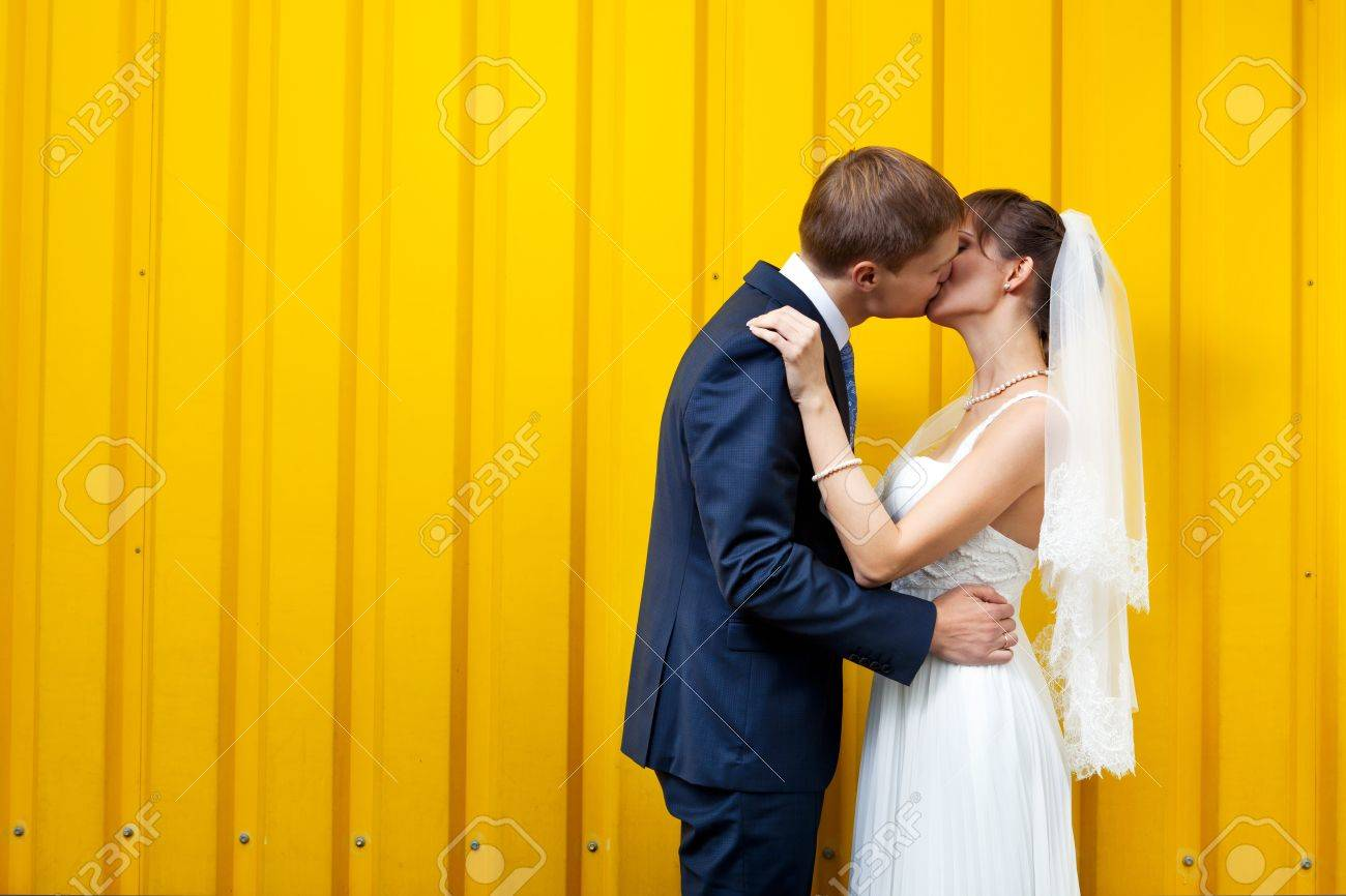Bride and groom kissing against yellow wall Stock Photo - 11792912