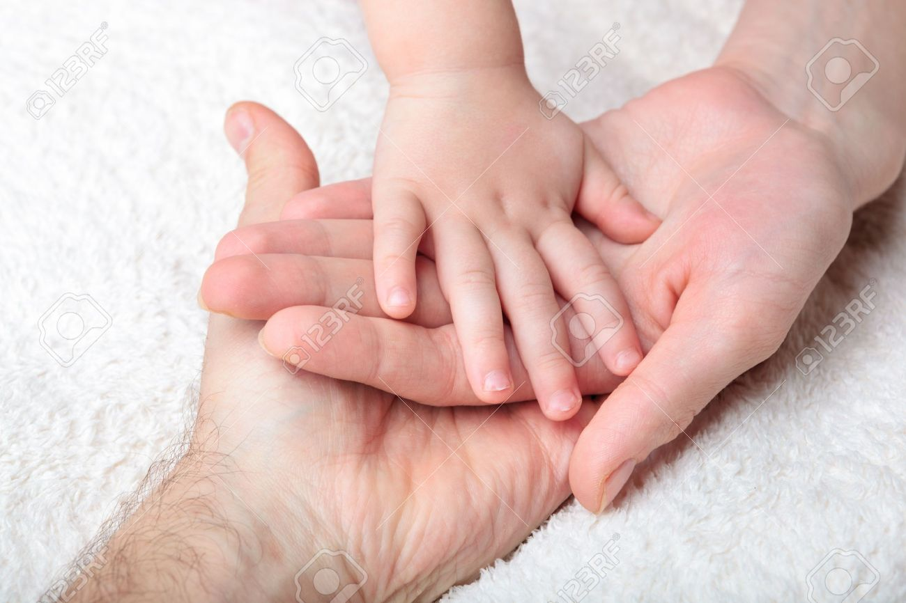 Closeup Of Baby Hand Into Mother And Father Hands Stock Photo