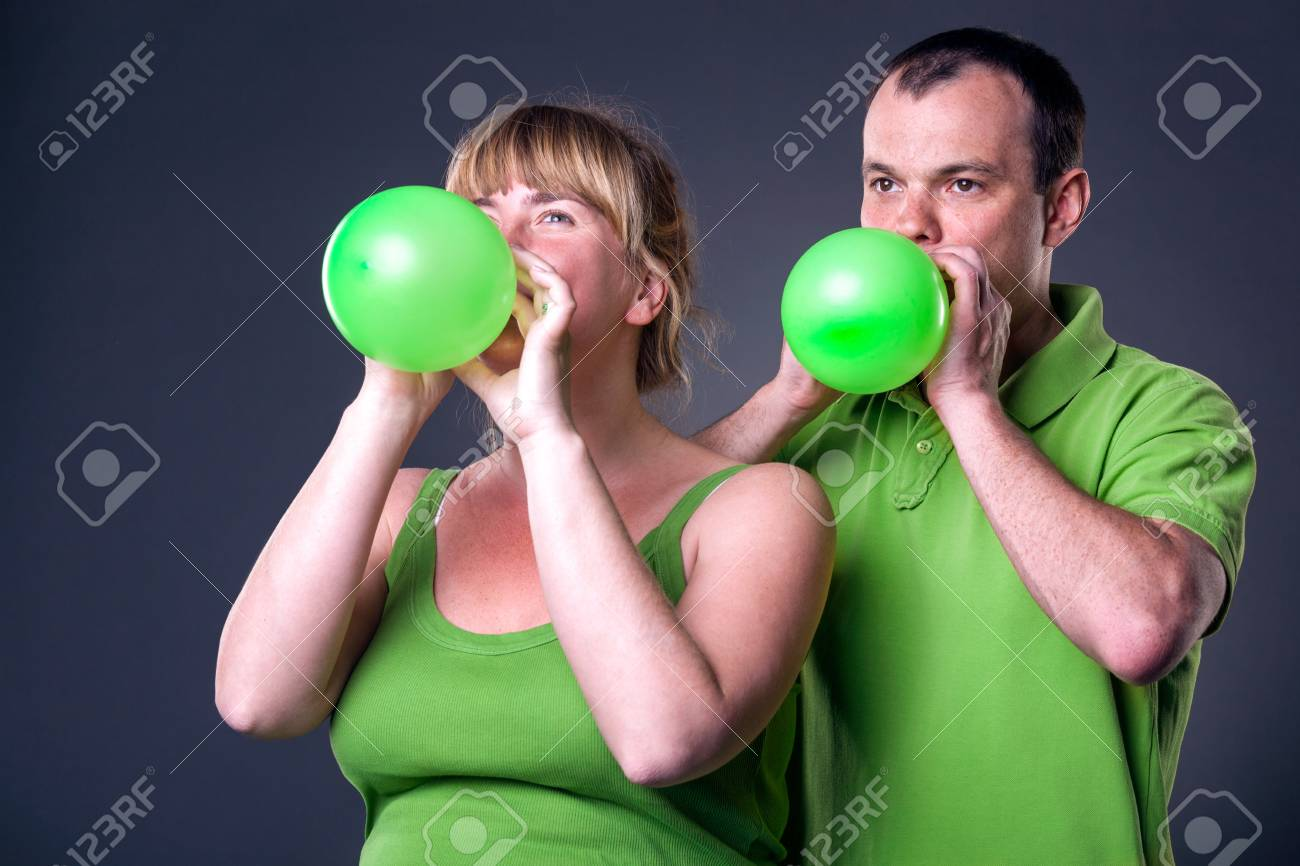 Happy young couple having fun with balloons - studio shot Stock Photo - 15038479