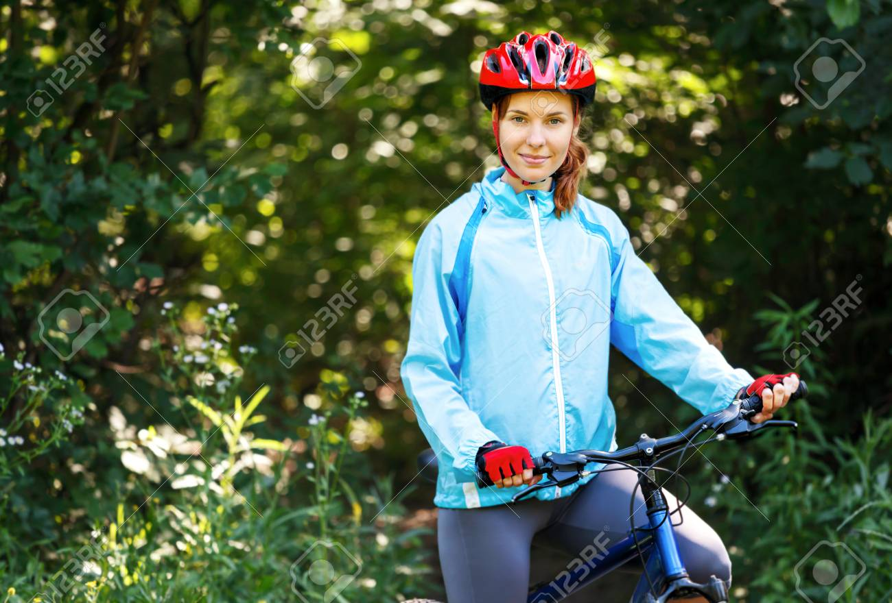 Portrait Of Happy Young Woman With Mountain Bike Outdoors