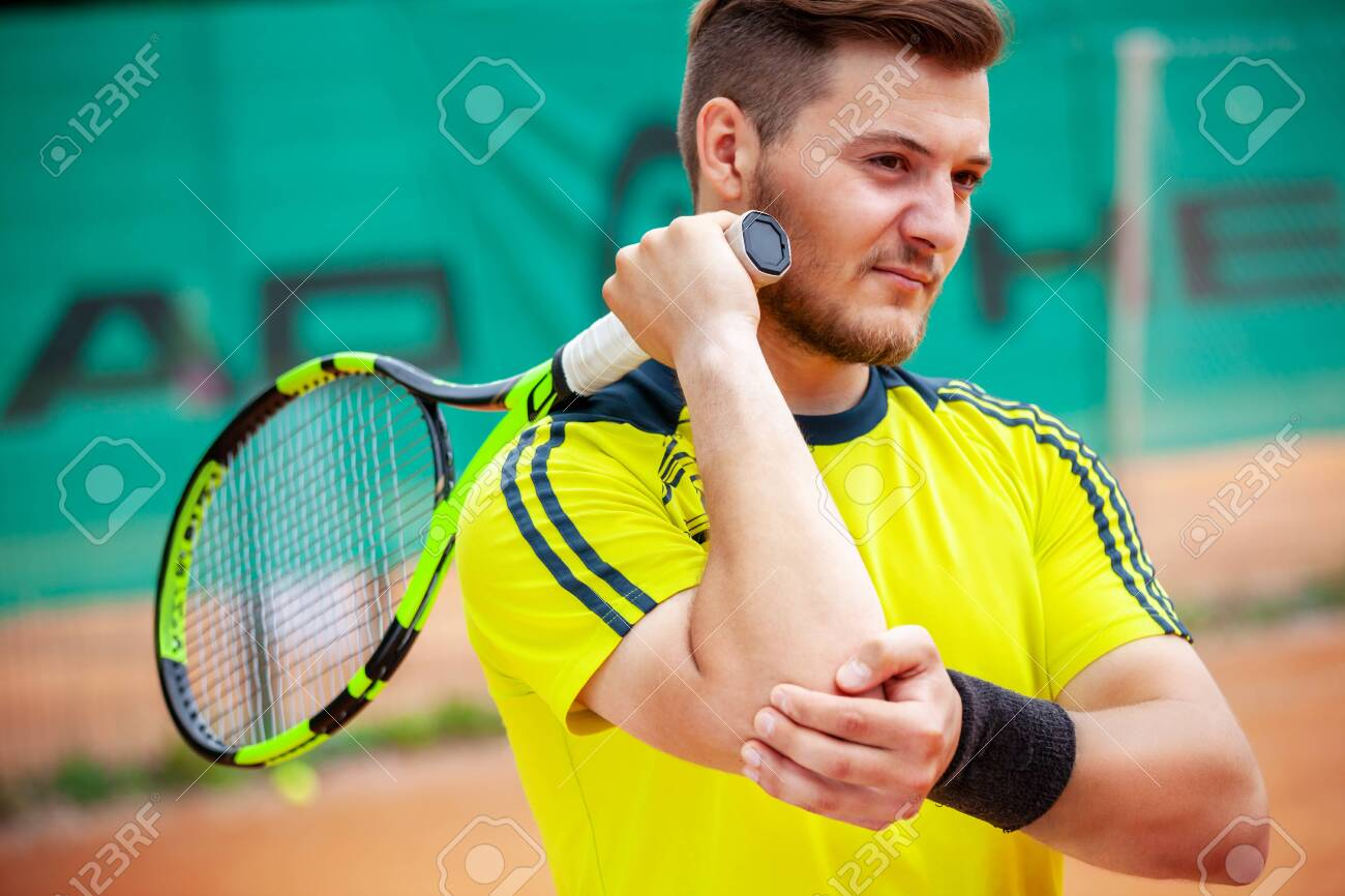 Male tennis player holding his injured elbow. Tennis elbow concept. - 131997960