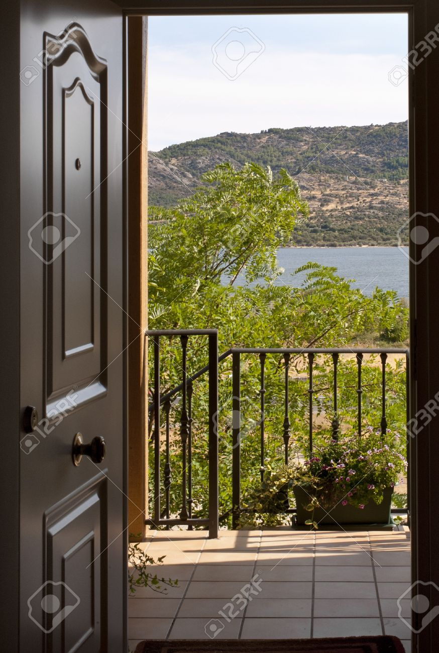 open house door. can see the open door of a home with balcony and lake in house