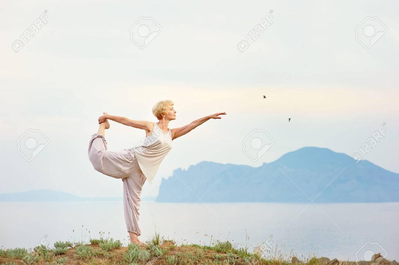 Senior woman doing yoga exercises with mountain on the background - 34185040