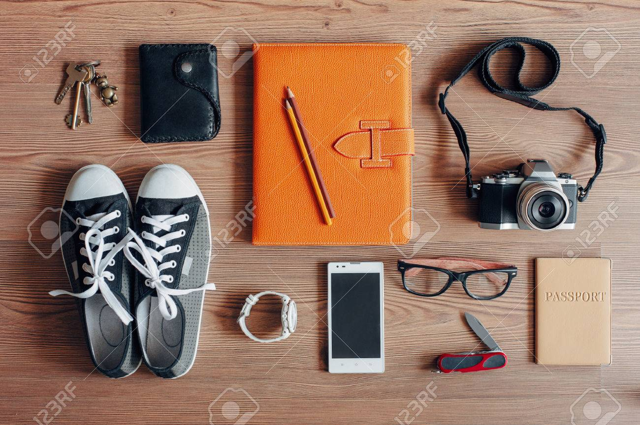 Outfit of traveler, student, teenager, young woman or guy. Overhead of essentials for modern young person. Different photography objects on wooden background. Items include keys, camera, smart phone, glasses, passport, digital tablet, wallet, folder, watc Stock Photo - 51114631