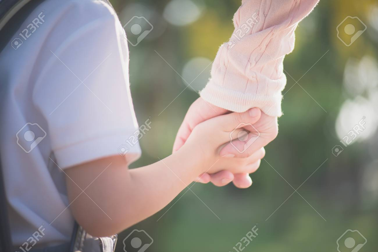 Asian mother holding hand of little son with backpack outdoors, back to school - 101412848