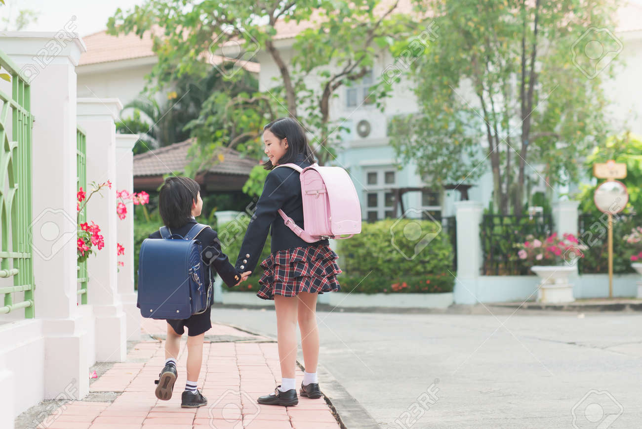 Cute Asian children holding hand together while going to the school - 168042982