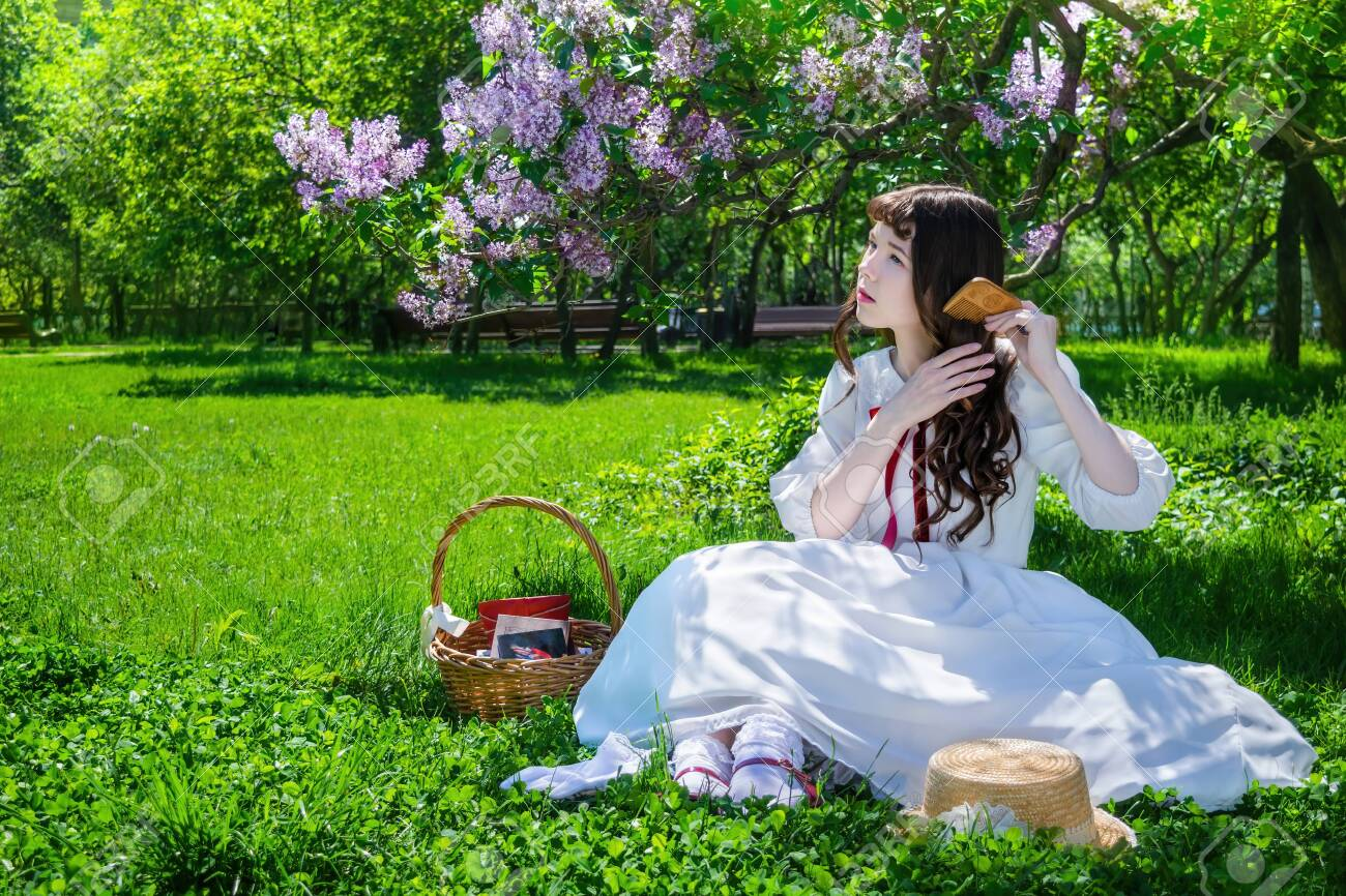 Nice girl in a white dress sits on a lawn in a park under a bush of blooming lilacs and combes her long hair. - 141159754