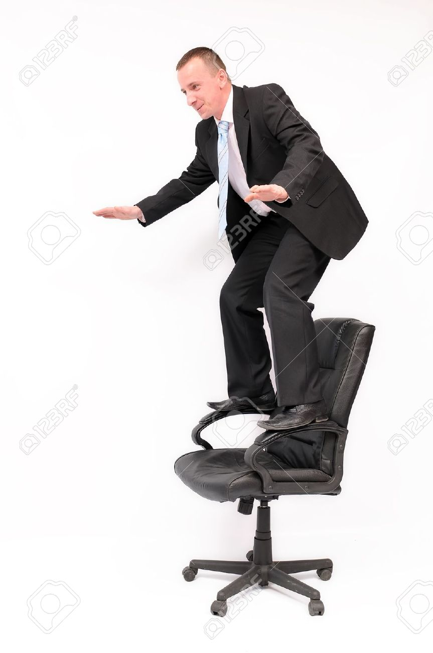 Standing Chair businessman standing on a chair trying to keep his balance. stock