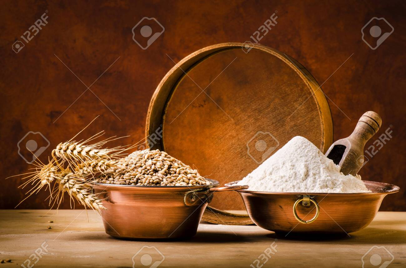 on the rustic wooden table some copper bowls with flour and wheat - 136915285