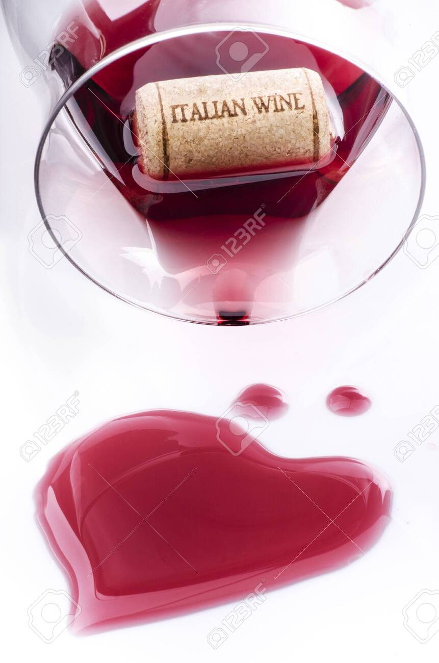 an inverted glass with red wine in which a cork stopper floats with the inscription Italian wine and spilled wine forming a heart - 137488217